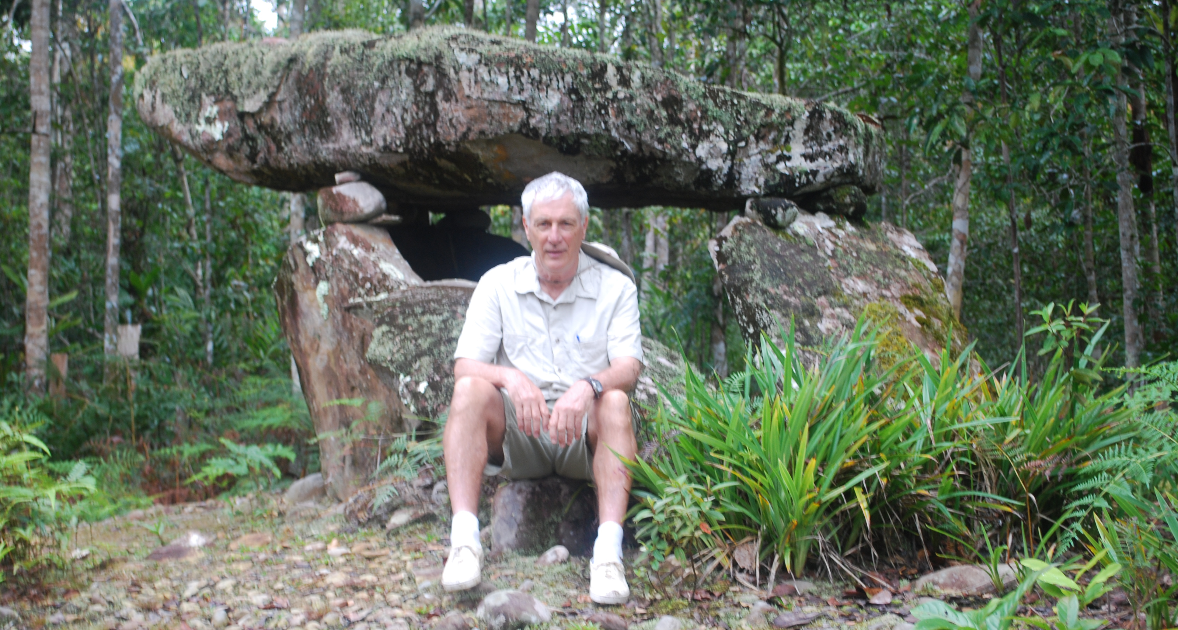 Paul Malone sitting in front of a megalith at Palungan